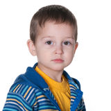 Serious kid in a striped blue and yellow jacket Royalty Free Stock Photos