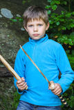 Serious kid with a wooden sword on stone Royalty Free Stock Photography
