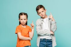 Free Serious Kids Pointing Up With Fingers Royalty Free Stock Photo - 221259685