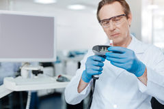 Serious lab assistant looking attentively at test glass Stock Photo