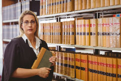 Serious lawyer holding a book. In library Stock Images