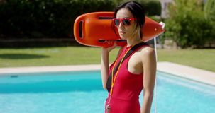 Serious lifeguard holding floatation device stock video