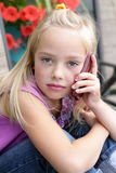 Serious little blond girl talking on a cellphone. A little young blond girl talking seriously on the cell phone, with long blond hair, shallow depth of field Royalty Free Stock Photography