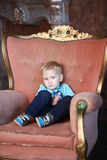 Serious little boy on the big chair Stock Photos