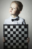 Serious Little boy with chessboard.fashion children.Bow-tie.Little genius Child Stock Image