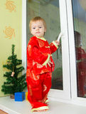 Serious little boy in Chinese holiday costume. Stands on window sill Royalty Free Stock Photos