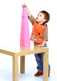 Serious little boy collects Red Pyramid in the Royalty Free Stock Photo