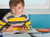 Serious little boy at the desk Stock Photos