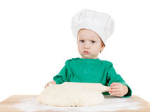 Serious little boy kneading dough for the cookies, isolated on white. Serious little cook boy kneading the dough for the cookies, isolated on white background Stock Photos