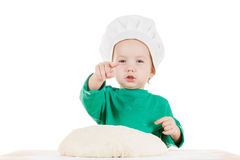 Serious little boy kneading dough for the cookies, isolated on white. Serious little cook boy kneading the dough for the cookies, isolated on white background Stock Image