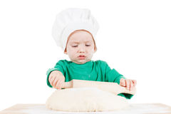 Serious little boy kneading dough for the cookies, isolated on white Stock Photo