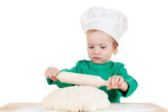 Serious little boy kneading dough for the cookies, isolated on white Royalty Free Stock Image
