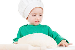 Serious little boy kneading dough for the cookies, isolated on white Royalty Free Stock Photo