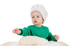 Serious little boy kneading dough for the cookies, isolated on white Royalty Free Stock Images