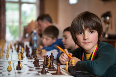 Serious little boy playing chess with other students Royalty Free Stock Images
