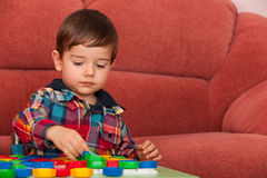 Serious little boy playing at the table royalty free stock image