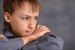 Serious little boy. Portrait of a serious little boy over a gray background stock photography