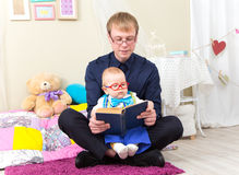 Serious little boy read an old book with his father in glasses. At home Stock Image