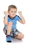 Serious little boy in shorts and blue t-shirt Stock Photos