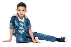 Serious little boy sits Stock Photography