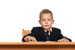 Serious little boy in suit at the desk Stock Photography