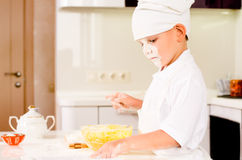 Serious little chef consulting his recipe book Stock Photos