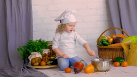 Serious little chef with a ladle cooking in the kitchen decorations. stock video