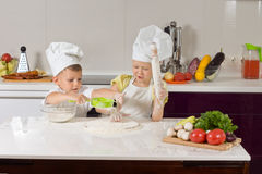 Serious Little Chefs Baking in Kitchen. Serious White Little Chefs Baking SOmething to Eat in Kitchen Stock Photography