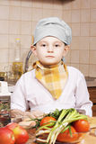 Serious little cook with tomatoes an apples Stock Images