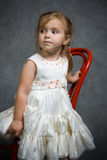Serious little girl. Little girl in a red chair Stock Photo