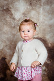 Serious little girl with blond hair and plump cheeks stock photography