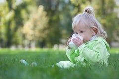 Serious little girl drinking milk Stock Photo
