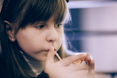 Serious little girl drinking orange juice using straw Stock Images