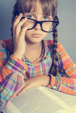 Serious little girl in glasses with a book Stock Images