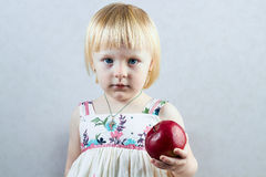 Serious little girl holds  a red apple Royalty Free Stock Photos