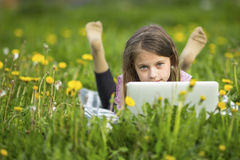 Serious little girl with laptop lying on green grass. Education. Stock Photo