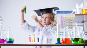 Serious little girl looking at color of reagent Royalty Free Stock Photo