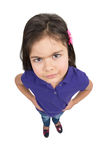 Serious little girl looking up. Little girl holding hands in pockets Royalty Free Stock Images