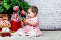 Serious little girl near christmass tree and her presents Royalty Free Stock Photography