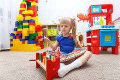 Serious little girl playing and eating banana in daycare Royalty Free Stock Images