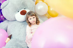 Serious little girl posing lying on big teddy bear Stock Photos