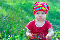 Serious little girl in red clothes sitting  in the middle grass Stock Photography