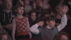Serious little girl singing and repeat after performers on scene in concert hall stock video footage
