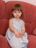 Serious little girl on the sofa Royalty Free Stock Photos