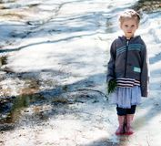 Serious little girl standing on the ice. Spring warm day.  royalty free stock photos