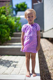 Serious little girl stands in front of her home Stock Photos