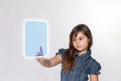 Serious little girl is touching a blank transparent rectangle Royalty Free Stock Photo