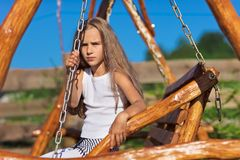 Serious little girl on wooden chain swing. Serious little girl with blond long hair sitting on wooden chain swing in rural playground Royalty Free Stock Photography