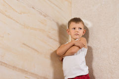 Serious Little Kid Isolated on Wooden Walls Royalty Free Stock Image