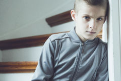 Serious lonely boy in gray jacket beside staircase Stock Images